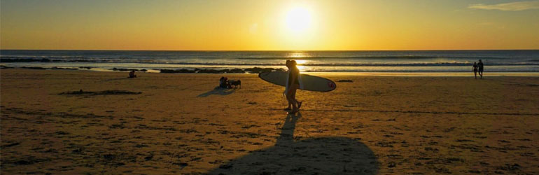 A person walks across a beach in Costa Rica holding a surfboard. The Sun is setting behind them and the whole sky is gold.