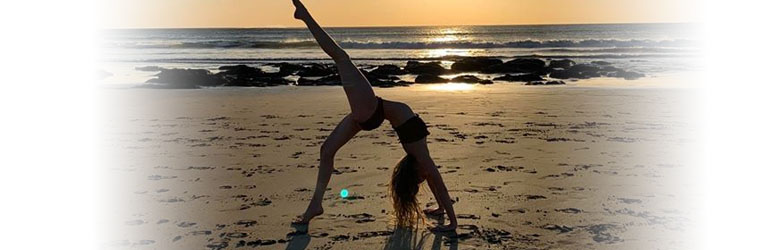 Woman doing yoga on a beach. She is doing a back bend with her leg raised.