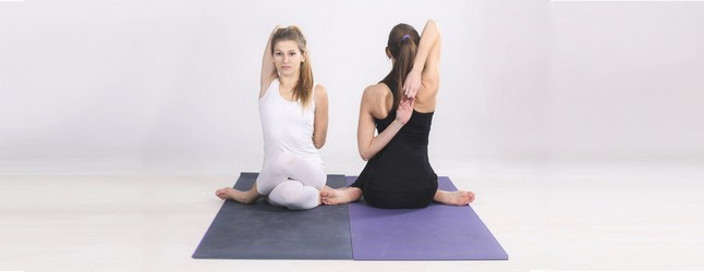 Two women do the cow face pose showing you both the front and the back of the pose.