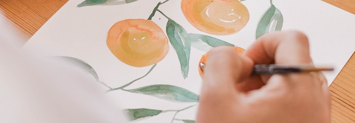 A person is using water paints to paint oranges.