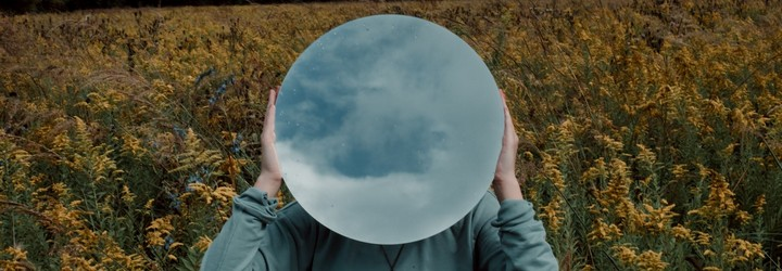 A person holds a mirror in front of their face that reflects the sky. This represents healing and opening the crown chakra.