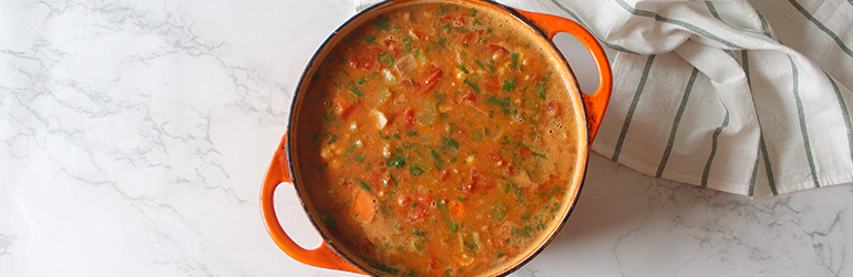 A soup pot is filled to the brim with delicious vegetable soup.