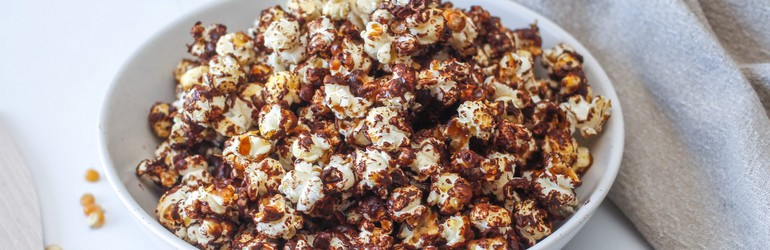 A close up of the dark chocolate and sea salt covered popcorn in a bowl.