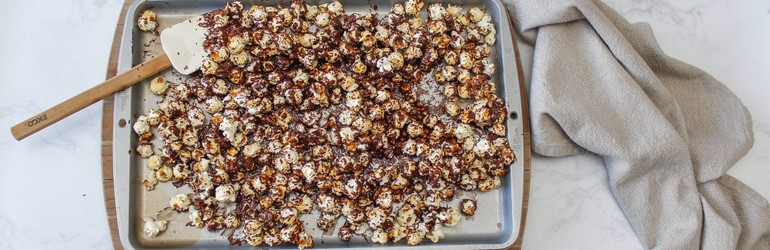 Popcorn and chocolate mixed on a baking sheet.