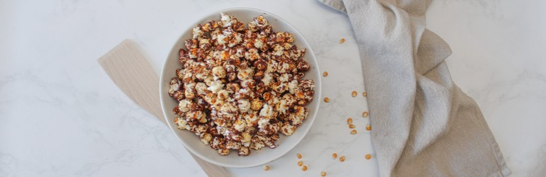 A top-down view of the chocolate and sea salt popcorn in a single serving bowl.