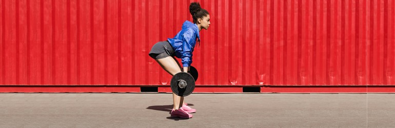 A woman deadlifts a barbell while facing to the right of the camera. She is standing in front of a red shipping container.