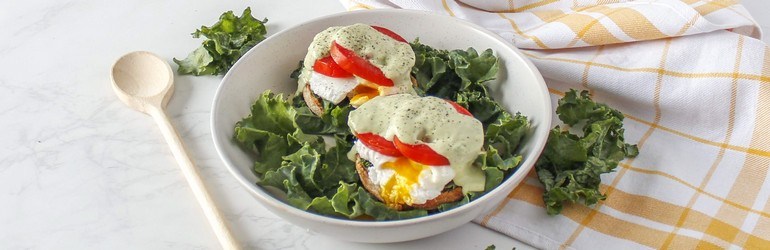 Eggs benedict on an English muffin and beautiful greens.
