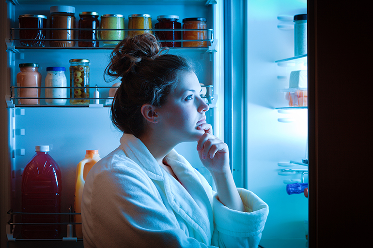 emotional woman looking in fridge for food