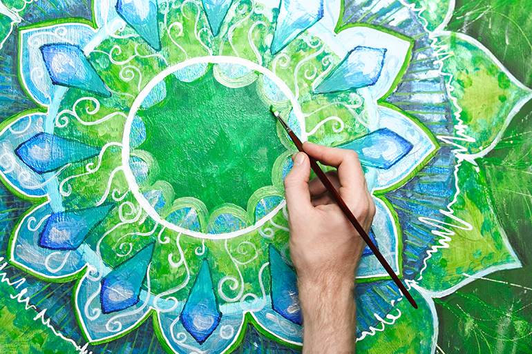 A hand paints a green mandala in reference to the heart chakra.