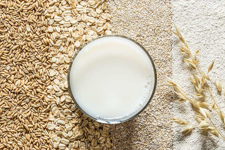 A glass of oat milk sits in a spread of different oats.