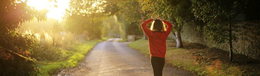 Brunette woman walks down a road.