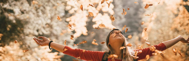 A woman throws leaves up into the sky while smiling.