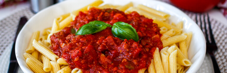 Pene bolognese in a bowl with basil on top.