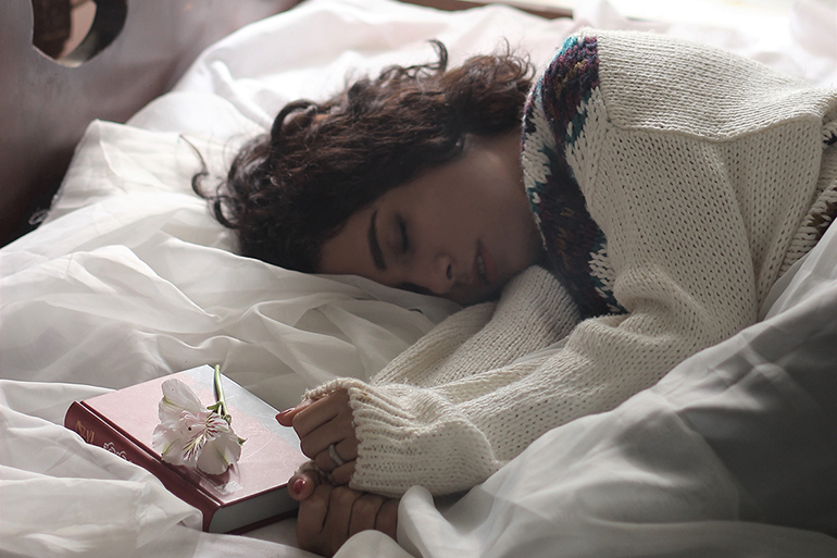 Woman sleeping in a white bed.
