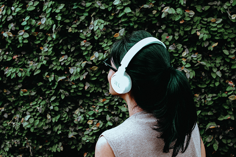 Woman whop is wearing white headphones. She is looking towards some green bushes that are the background in this photo.