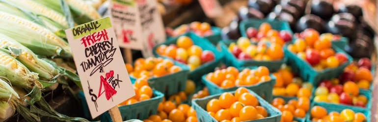 Cherry tomatoes at a grocery market in little green baskets.