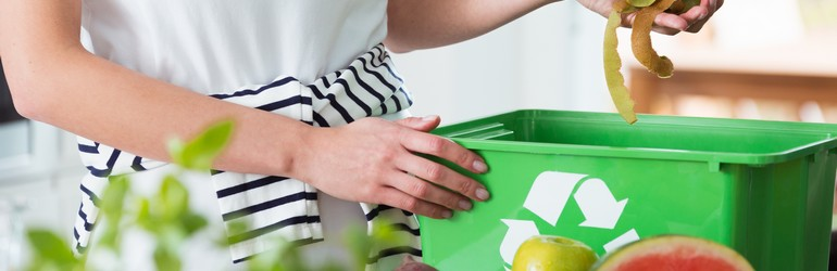 Someone recycling into a green bin.