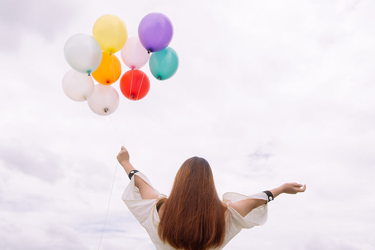 soulful woman holding rainbow balloons