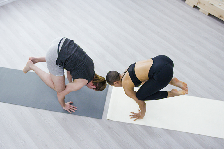 two people doing balancing yoga poses