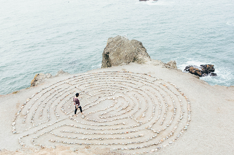 A person walking through a rock maze on a beach.