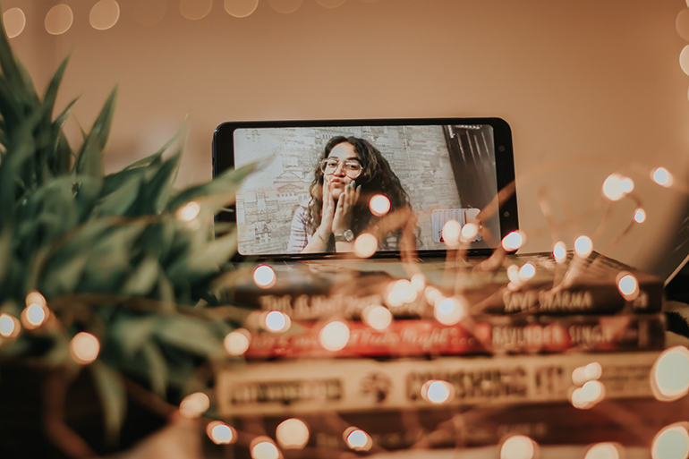Woman is on facetime behind a bunch of fairy lights. They are bonding through digital connections.