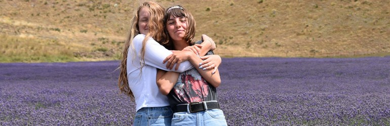 Two girlfriends hugging in a field of lavender. They are laughing and holding each other tightly while looking at the camera.