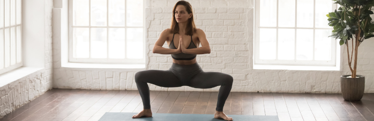 A woman in low goddess pose on a yoga mat.
