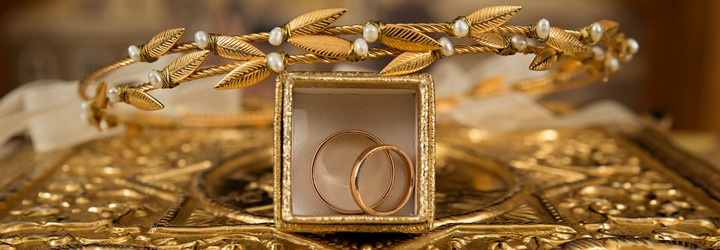 Some gold jewelry sit on a gold table. Pictured: Two gold rings in a golden box and a golden leaf covered tiara.