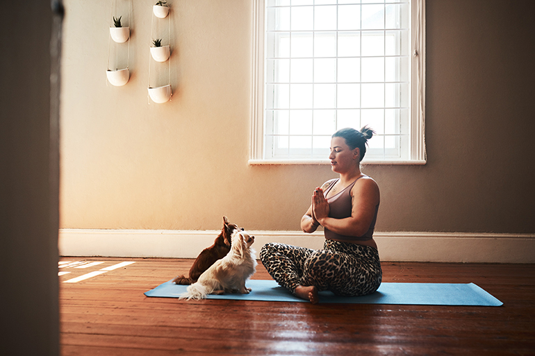 A woman meditates while sitting on her yoga mat on the floor with her two dogs sitting in front of her.