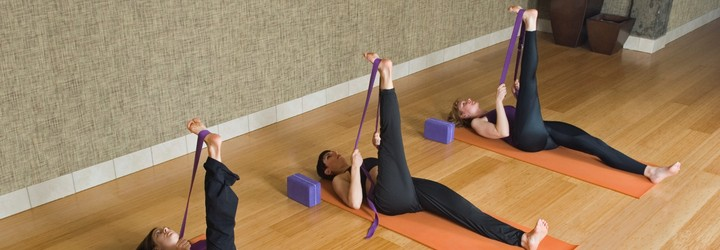 3 people in a yoga studio doing a laying hamstring stretch with a yoga strap.