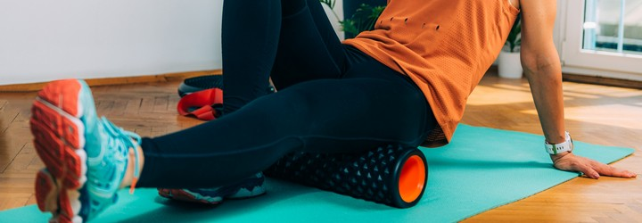 A woman rolling the back of her thigh with a foam roller to stretch her tight hamstrings.