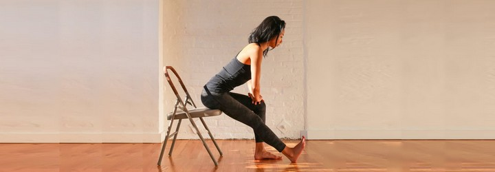 A woman stretches her hamstrings while sitting on a chair.