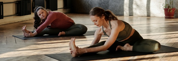 Two people stretching on yoga mats.