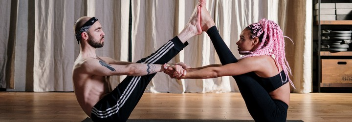 Two people doing a v-sit while holding hands.