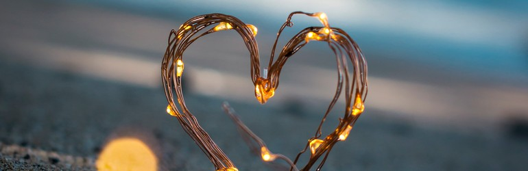 Fairy lights wrapped around a bundle of twigs that has been bent into a heart shape. This is in front of a sunset on a beach. It is twlight hour.
