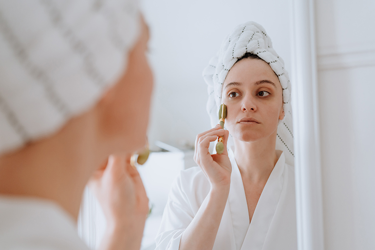 A person stands at a mirror with a towel on their head. They are using a jade roller to get rid of redness and puffiness in their face.