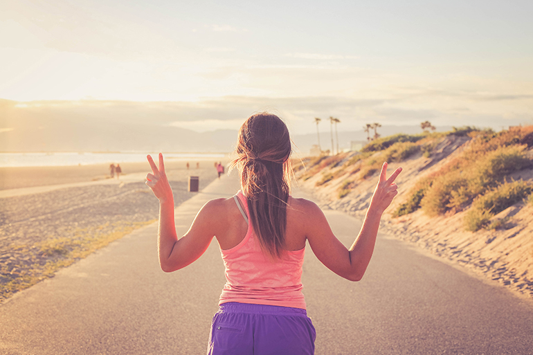 woman going on a jog holding up peace signs