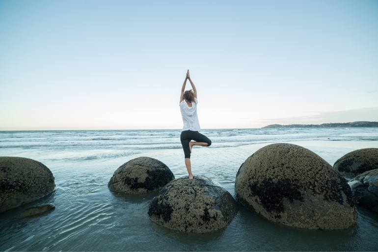 A woman is standing on some rocks next to the ocean doing a tree yoga pose.