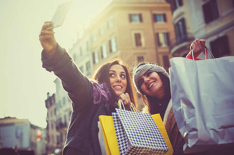 two women enjoying black friday shopping taking a selfie