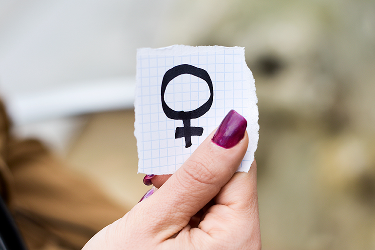 woman holding paper with female gender symbol