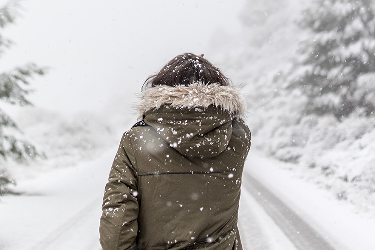 Woman standing in snow facing out at the landscape.