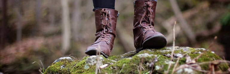 A person standing in nature in hiking boots.