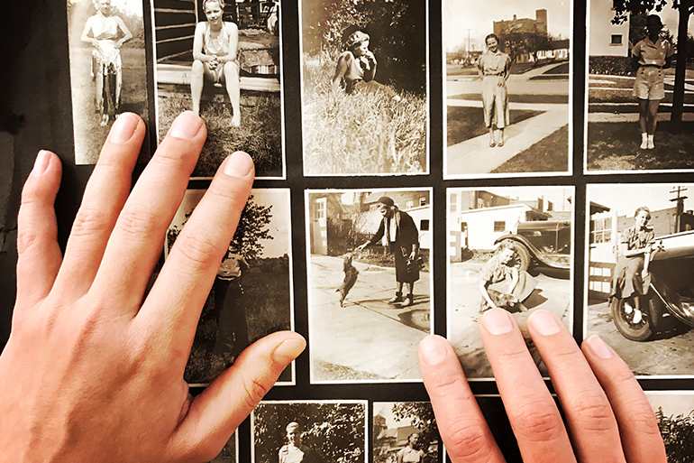 person looking at old photographs to heal past lives