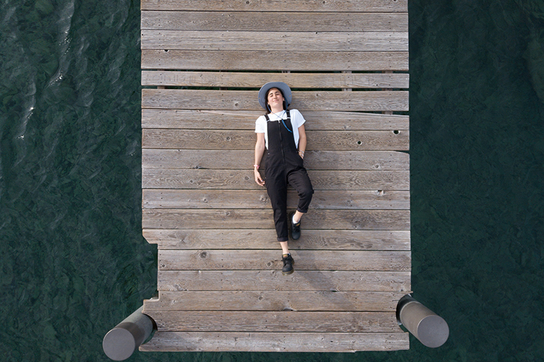 A woman lays on the end of a dock staring up at the sky.