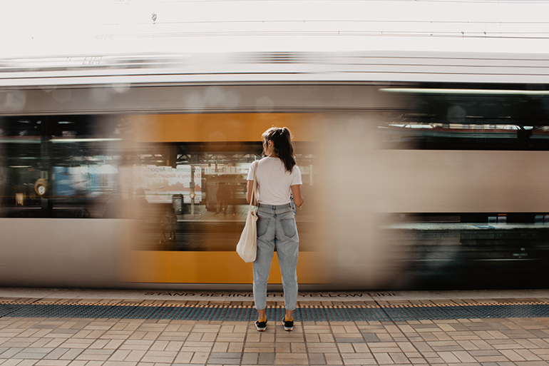 Woman standing in front of a speeding train.