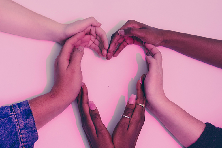 Five people making a heart against a white wall with their hands.