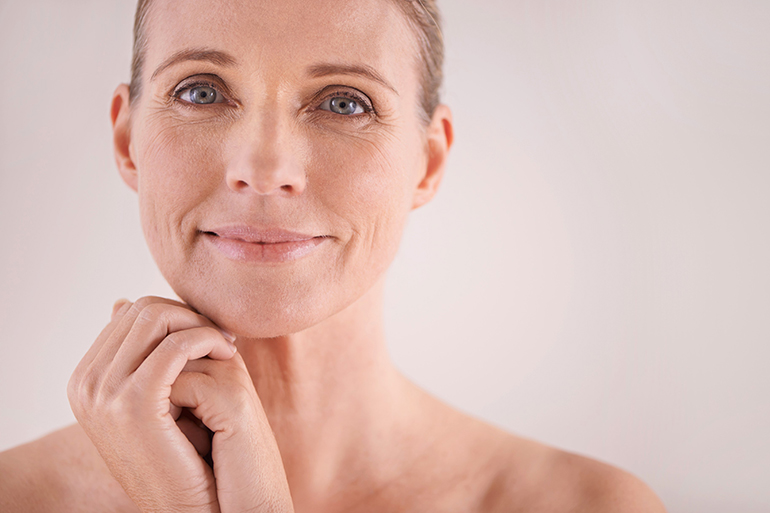 A woman showing her natural skin. She is looking towards the viewer showing her crows feet and wrinkles.