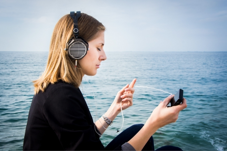 A woman sits next to a serene ocean scene listening to music with her headphones in.