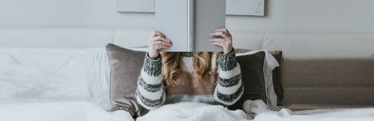 A woman is curled up in bed under a cozy blanket reading a grey book.