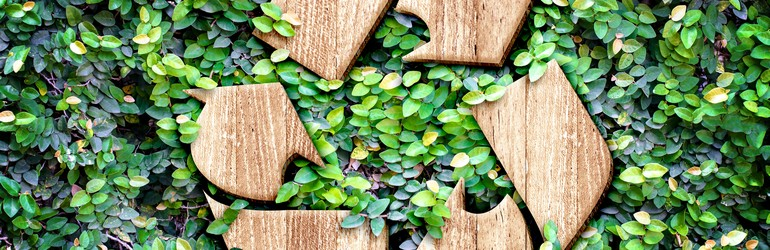 A wooden recycling symbol surrounded by a pile of leafs.